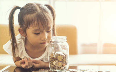 Child looking at savings jar