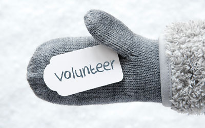 Person holding a volunteer sign