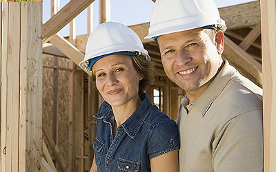 happy family standing in a home being built