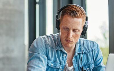 Young man sitting with head phones who needs Kwik Cash