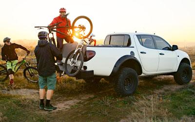 mountain bikers loading bikes into a white truck