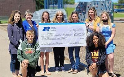 Kids holding a big check