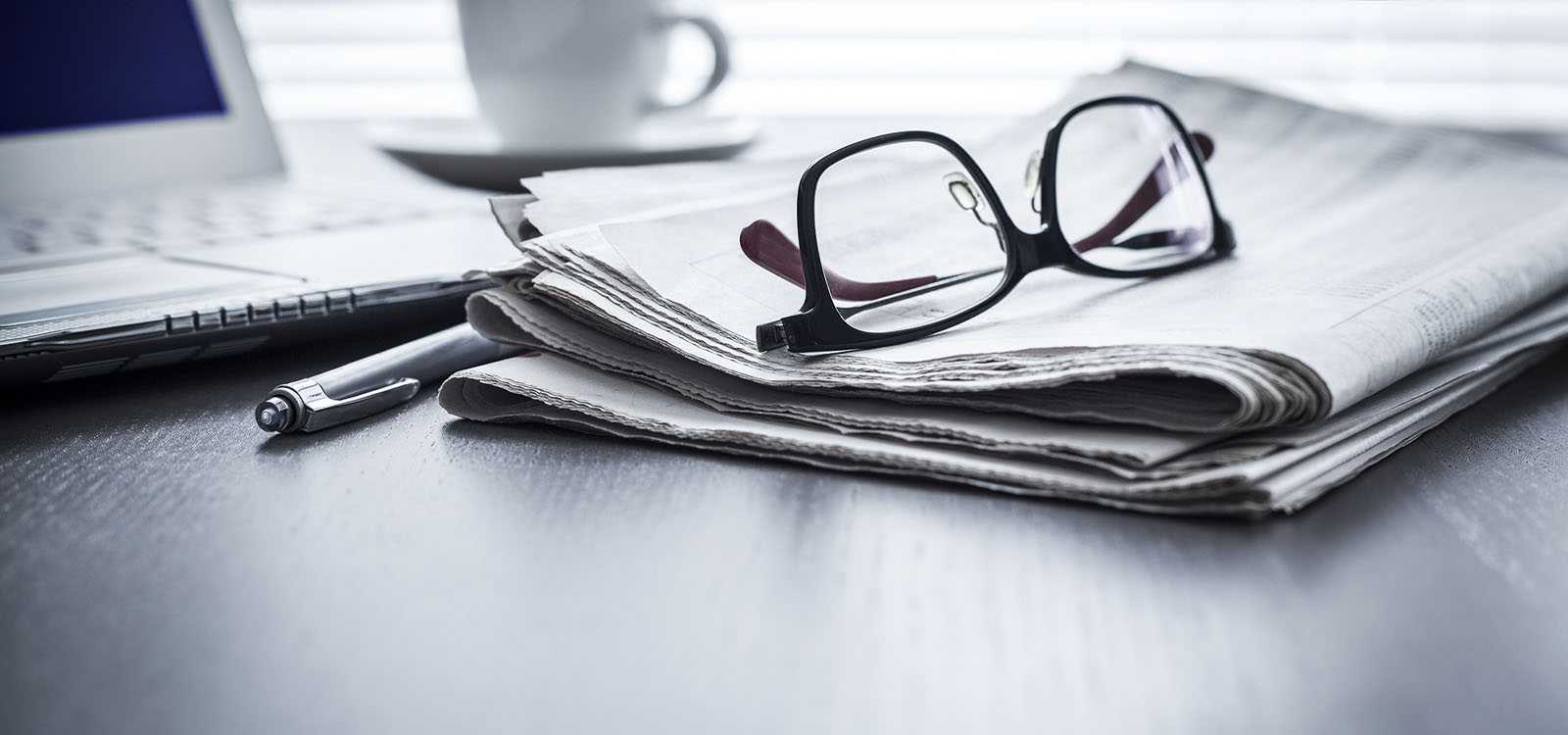 Glasses, computer and newspaper