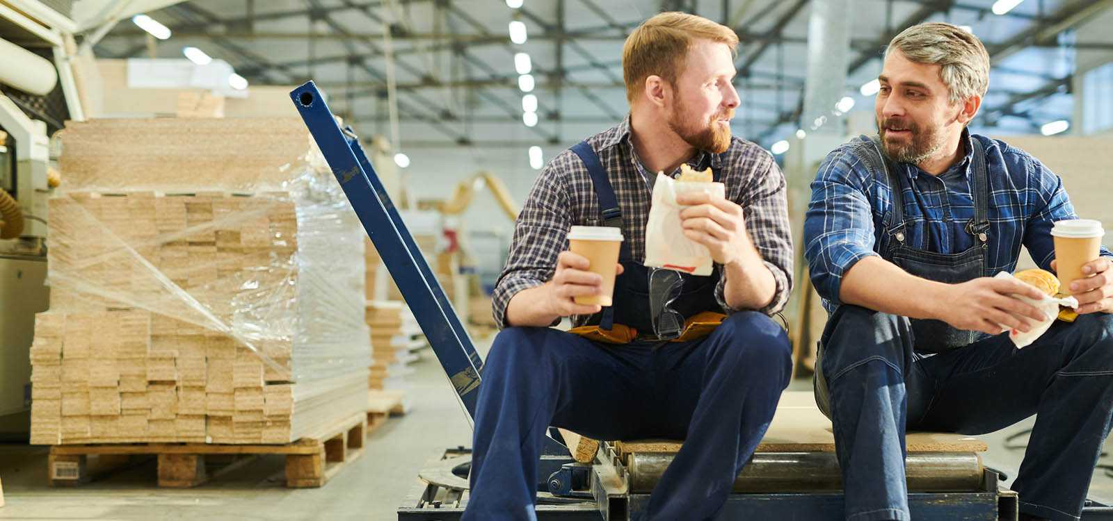 two men in warehouse eating