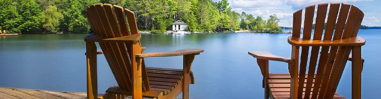 Two empty chairs in front of a lake
