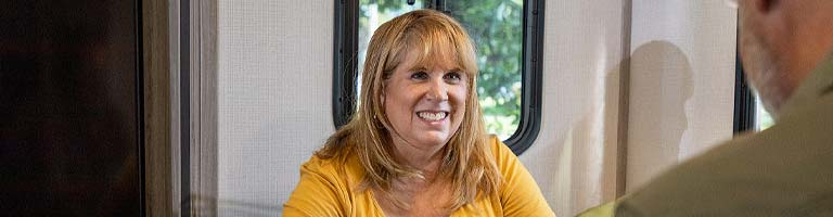 man and woman sitting in trunk of car next to house