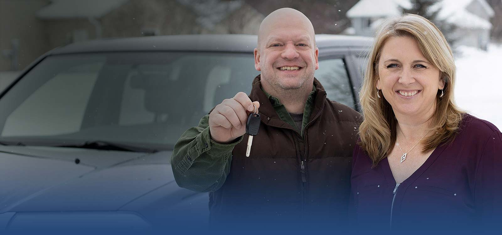 Couple holding keys in front of new car